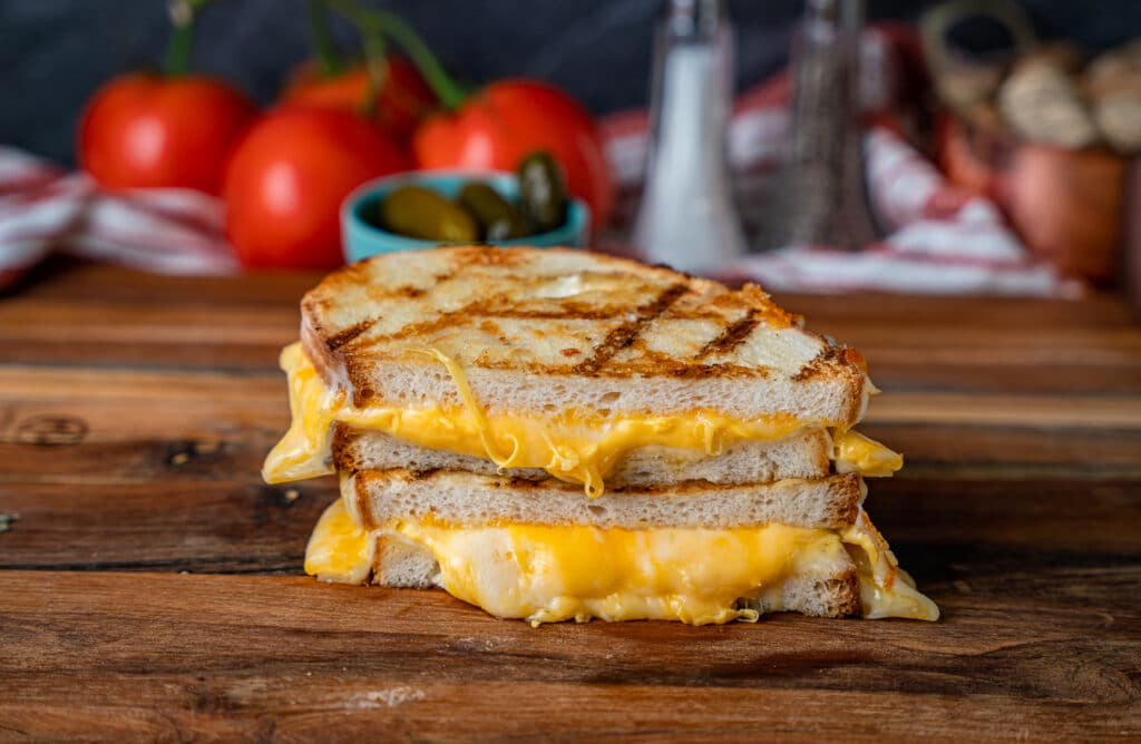 cheese oozing out of a grilled cheese sandwich made on the grill