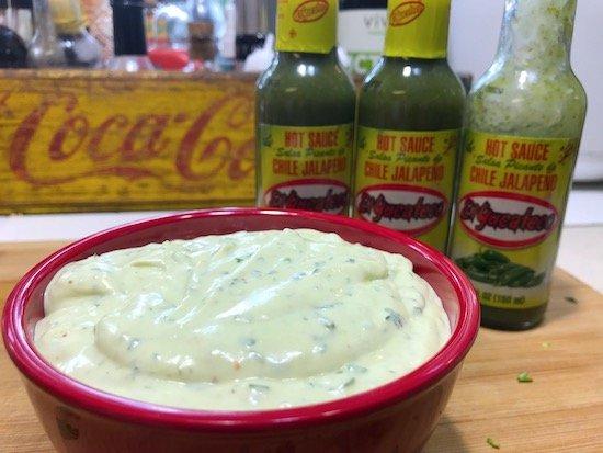 Avocado Jalapeño Crema in bowl with jalapeno bottles