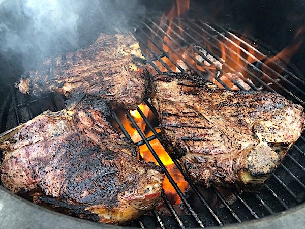 T bone steaks on the grill after being cleaned with Crazy Mazie Wooden Grill Scraper