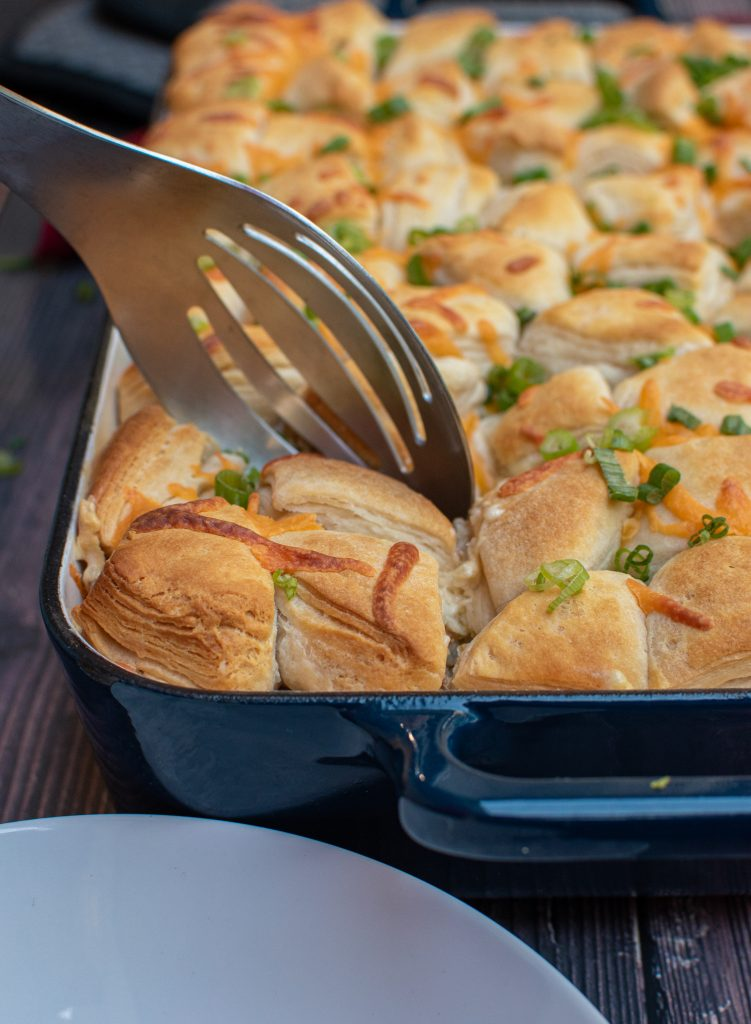 spoon scooping a portion of chicken pot pie topped with biscuits