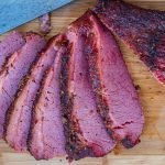 Smoked corned beef sliced on wooden cutting board