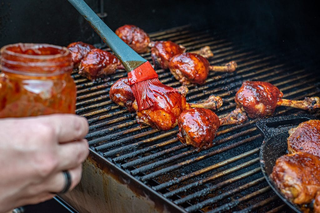 brushing barbecue sauce on chicken drumstick lollipops