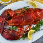 Cold water lobster served on a plater with drawn butter and lemon wedges