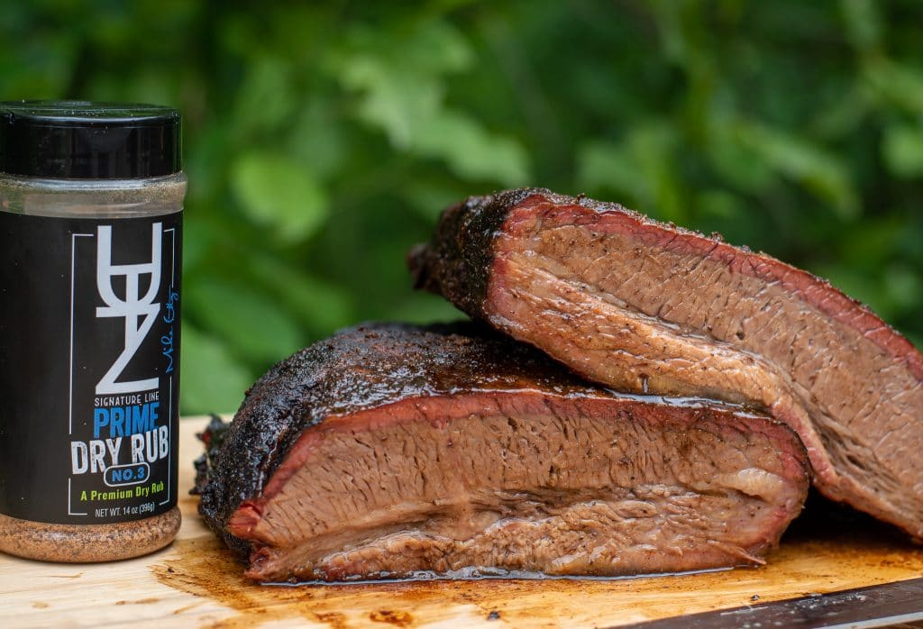 Smoked beef brisket cut in half to show smoke ring with Utz works dry rub