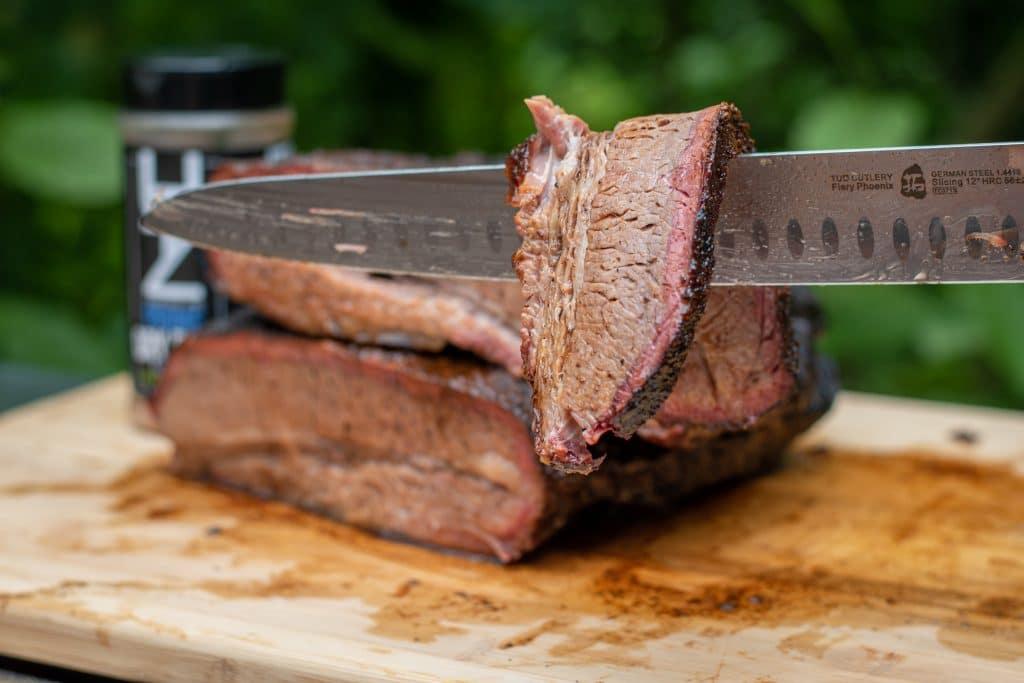 knife holding slice of brisket