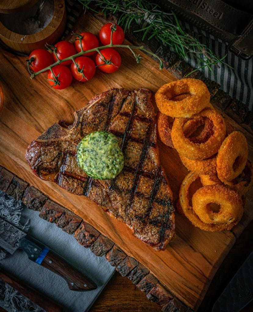 Grilled t bone steak using a charcoal grill with onion rings on the side