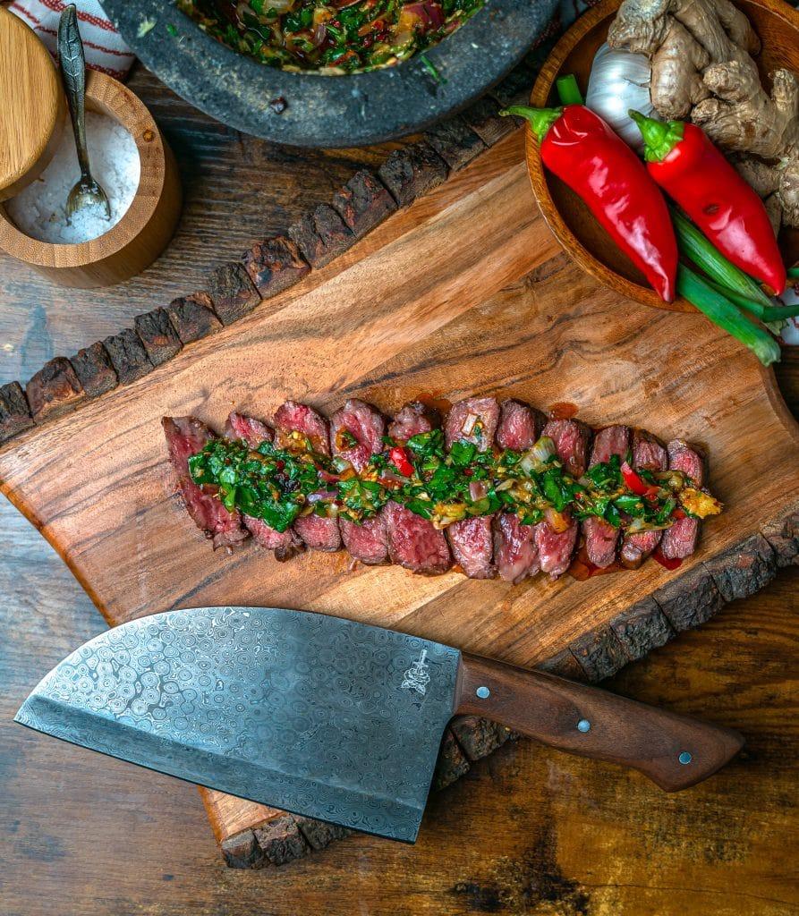 sliced rare Denver Steak topped with chimichurri sauce