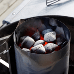 Charcoal chimney filled with charcoal briquettes