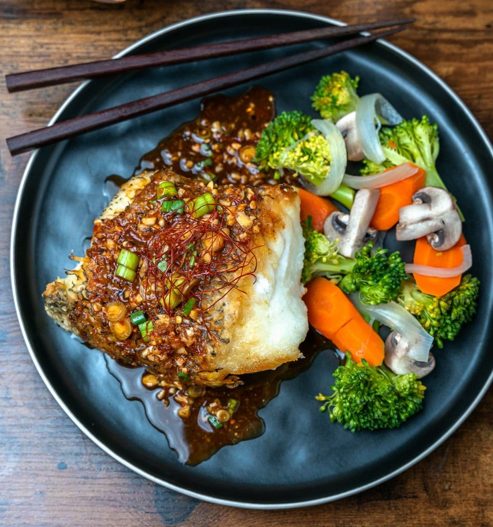 Pan seared Chilean Sea Bass topped with spicy hoisin vinaigrette with seamed veggies