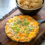 keto buffalo chicken dip served in a cast iron skillet with pork rinds
