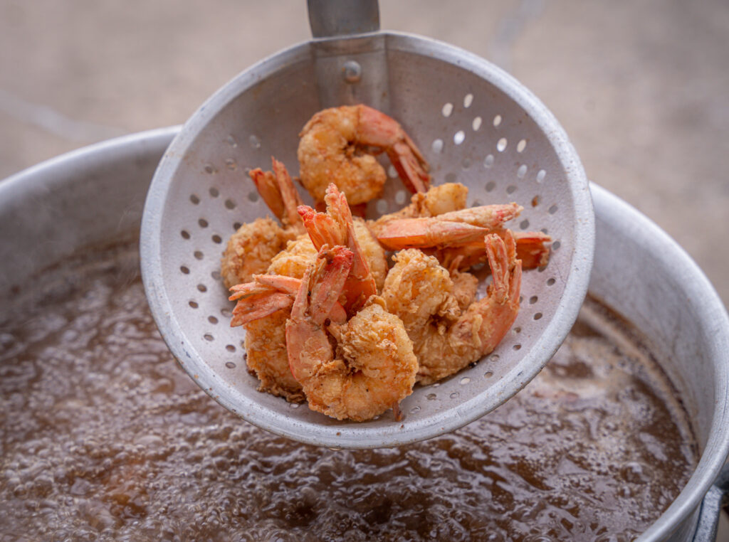 scooping out fried shrimp out of the hot oil