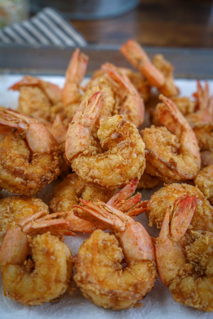 pile of crispy deep fried shrimp on paper towels