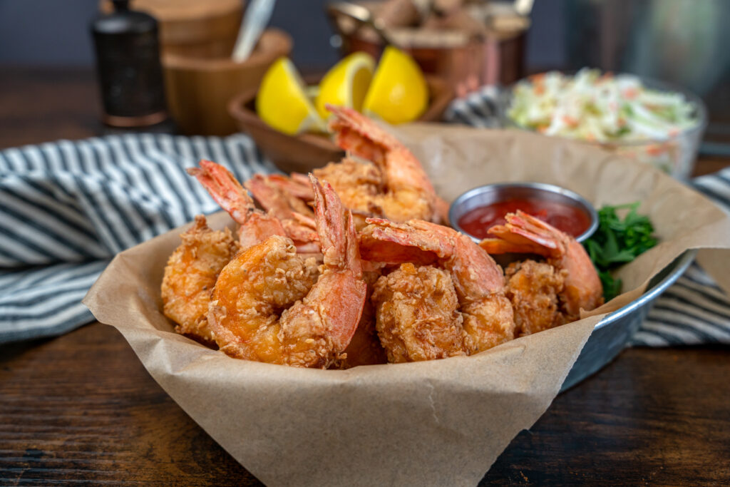 fried shrimp in a basket served with cocktail sauce