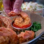 fried shrimp dunked into cocktail sauce