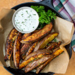 steak fries served in a cast iron skillet with brown parchment paper