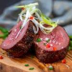 sliced beef tenderloin garnished with diced peppers chives and scallions