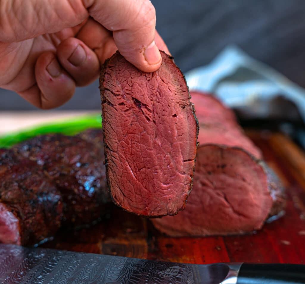 picking up a slice of beef tenderloin