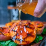 pouring sriracha honey glaze out of a small jar onto a grilled peach half