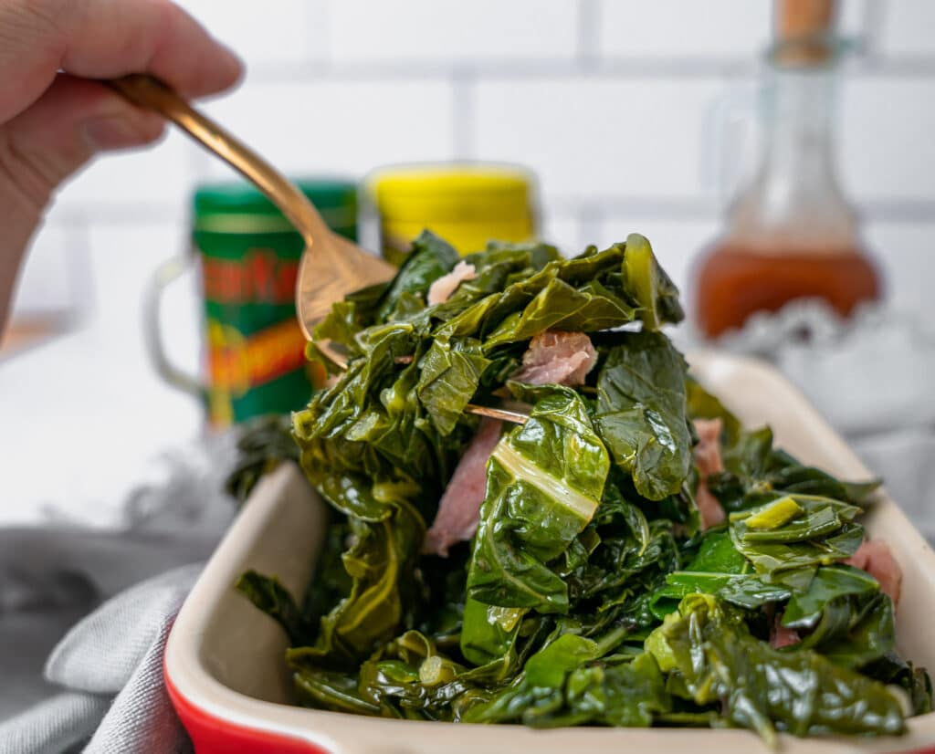 using a serving fork to scoop up southern collard greens with smoked turkey legs