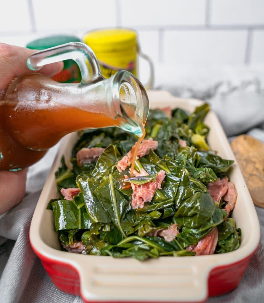 pouring Carolina vinegar bbq sauce over collard greens