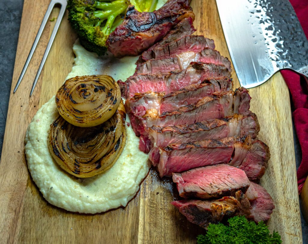 sliced ribeye on a cutting board with grilled onions and mashed potatoes