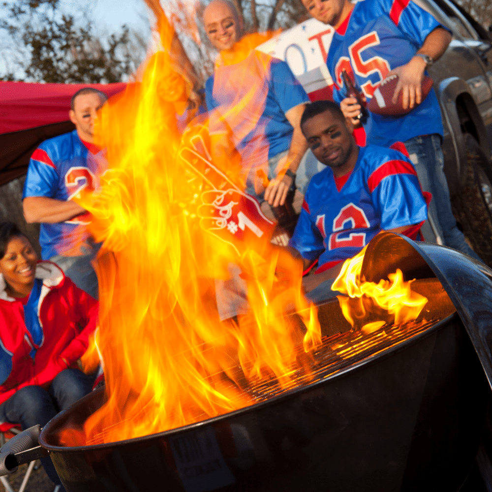 fire coming out of a grill at a tailgate