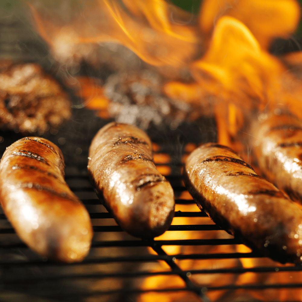 brats on a grill with flames